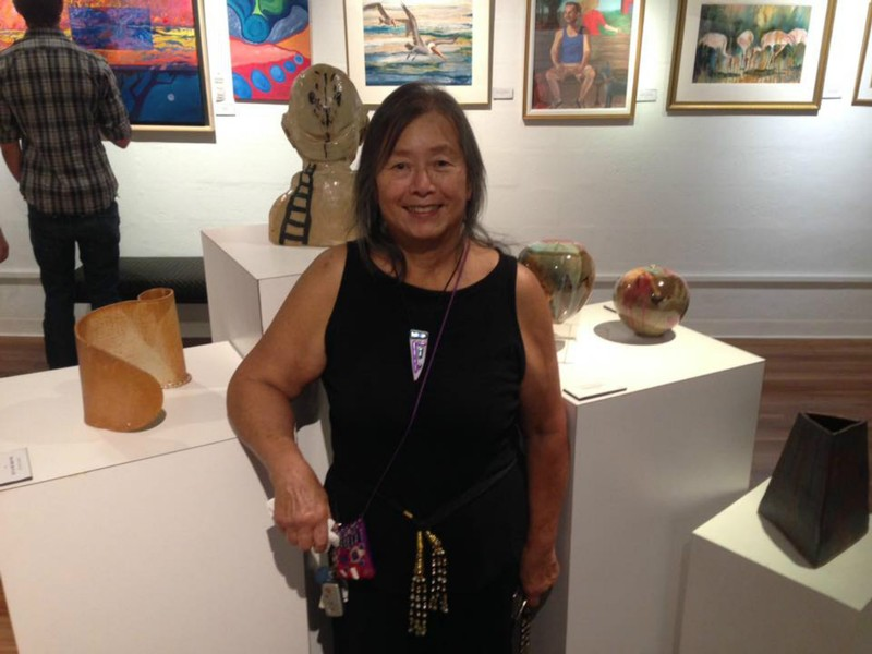 Mavis Jan-Lai and her two ceramic vessels at the Art Center Manatee. Her works are the one on her right and the hand built piece on her left!